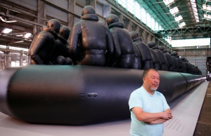 Chinese artist Ai Weiwei stands in front of his artwork consisting of a 60-metre rubber raft installation titled 'Law of the Journey' which includes around 300 figures representing refugees, during a media call for the Biennale of Sydney in Australia