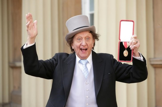 Entertainer Ken Dodd poses for photographers after being made a Knight Bachelor of the British Empire by Britain's Prince William at an investiture at Buckingham Palace in central London