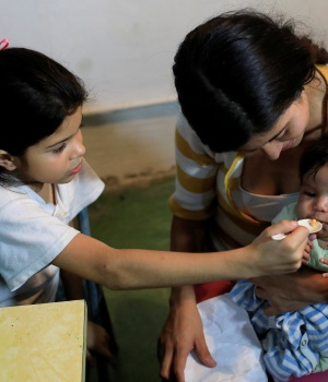Osiris, daughter of Viviana Colmenares, feeds her sister Ornella in a community diner at the slum of Petare in Caracas