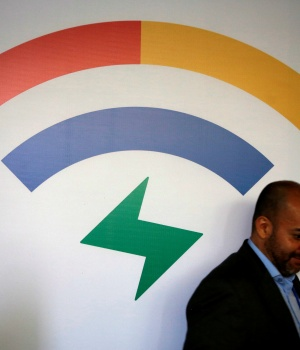 Man walks by the logo of Google Station before a news conference in Mexico City