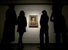 "Members of Christie's staff pose for pictures next to Leonardo da Vinci's ""Salvator Mundi"" painting in London"
