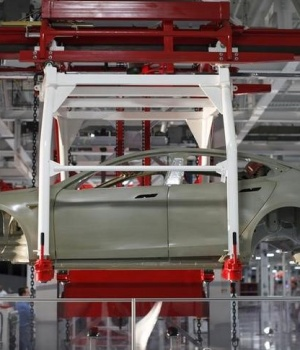 The body of a Tesla Model S is transported by an automated crane at the Tesla factory in Fremont