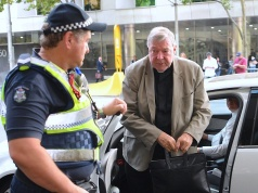 Vatican treasurer Cardinal George Pell is assisted by an Australian policeman as he gets out of a car upon arriving at the Melbourne Magistrates' Court