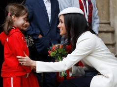 Britain's Prince Harry's fiancee Meghan Markle receives a bouquet of flowers after attending the Commonwealth Service at Westminster Abbey in London