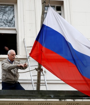 A man takes the flag off the flagpole outside the consular section of Russia's Embassy in London