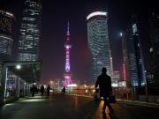 A man walks on a bridge in the financial district of Pudong in Shanghai