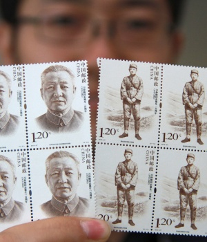 A man poses for pictures as he holds postage stamps of Xi Zhongxun, China's former vice premier and father of China's President Xi Jinping, in Yantai