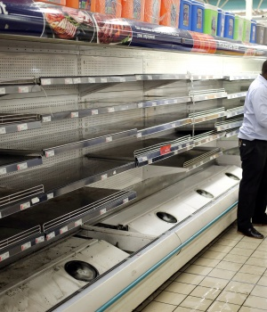 A worker looks at empty shelves after removing processed meat products at a Pick n Pay Store in Johannesburg