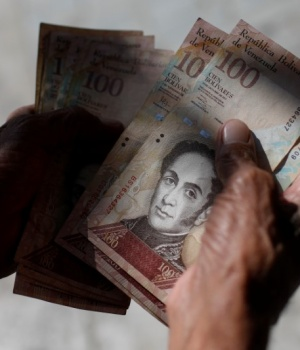 A man counts Venezuelan bolivar notes in downtown Caracas