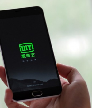 Photo illustration shows a person holding a phone with Baidu Inc's video streaming service iQiyi in Jinan
