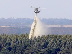 A helicopter drops water on a forest as a bushfire burns nearby, on the outskirts of the town of Cobden