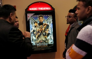 "A group of men gather in front of a poster advertising the film ""Black Panther"" on its opening night of screenings at the AMC Magic Johnson Harlem 9 cinemas in Manhattan"