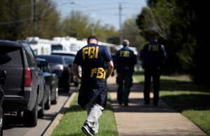 FBI agents walk towards a crime scene on Mission Oaks Boulevard following an explosion in Austin
