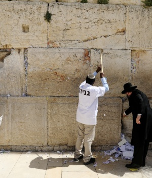 Men, including Western Wall Rabbi Shmuel Rabinowitz, clear notes placed in the cracks of the Western Wall, Judaism's holiest prayer site, to create space for new notes ahead of the Jewish holiday of Passover, in Jerusalem's Old City