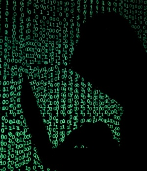 Hooded man holds laptop computer as cyber code is projected on him in this illustration picture