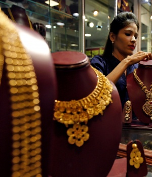 A salesperson attends to customer, inside a jewellery showroom during Akshaya Tritiya, a major gold-buying festival, in Mumbai