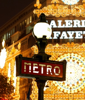 View of a metro sign in front the Galeries Lafayette department store with Christmas lights in Paris