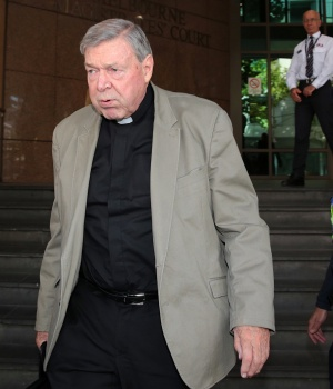 Vatican treasurer Cardinal George Pell is watched by a security guard and Australian police officer as he leaves Melbourne Magistrates' Court
