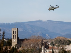A military helicopter flies over the village of Trebes after a hostage situation in a supermarket