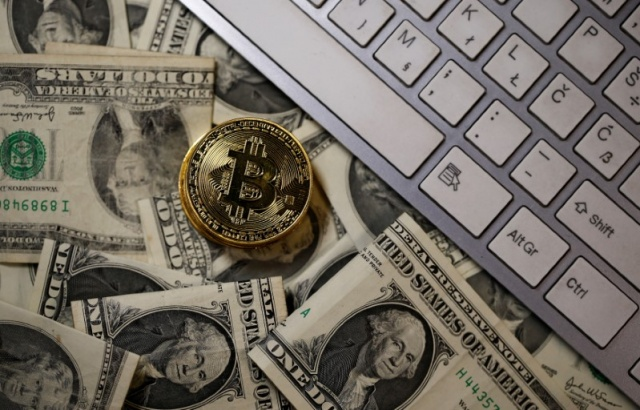 A bitcoin (virtual currency) coin placed on Dollar banknotes is seen in this illustration picture