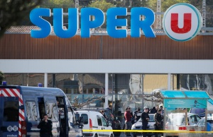 A general view shows gendarmes and police officers at a supermarket after a hostage situation in Trebes
