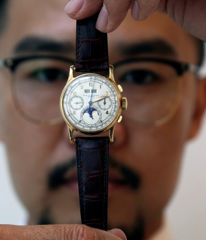 Exhibitor displays the Patek Philippe 18k gold perpetual chronograph wrist watch with moon phases belonging to the King Farouk, at the Christie's auction in Dubai