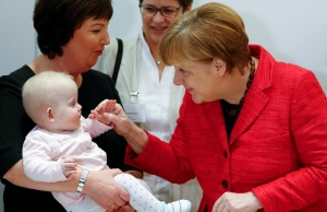 German Chancellor Merkel grabs the hand of a triplet baby girl in Berlin