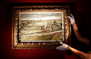 "Artcurial's employee poses as he holds the painting ""Raccommodeuses de filets dans les dunes, 1882"" (Women Mending Nets in the Dunes) by painter Vincent Van Gogh during a preview for media at Artcurial Auction House in Paris"
