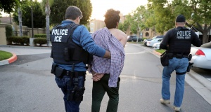 U.S. Immigration and Customs Enforcement (ICE) Assistant Field Office Director Jorge Field (L), 53, arrests an Iranian immigrant in San Clemente
