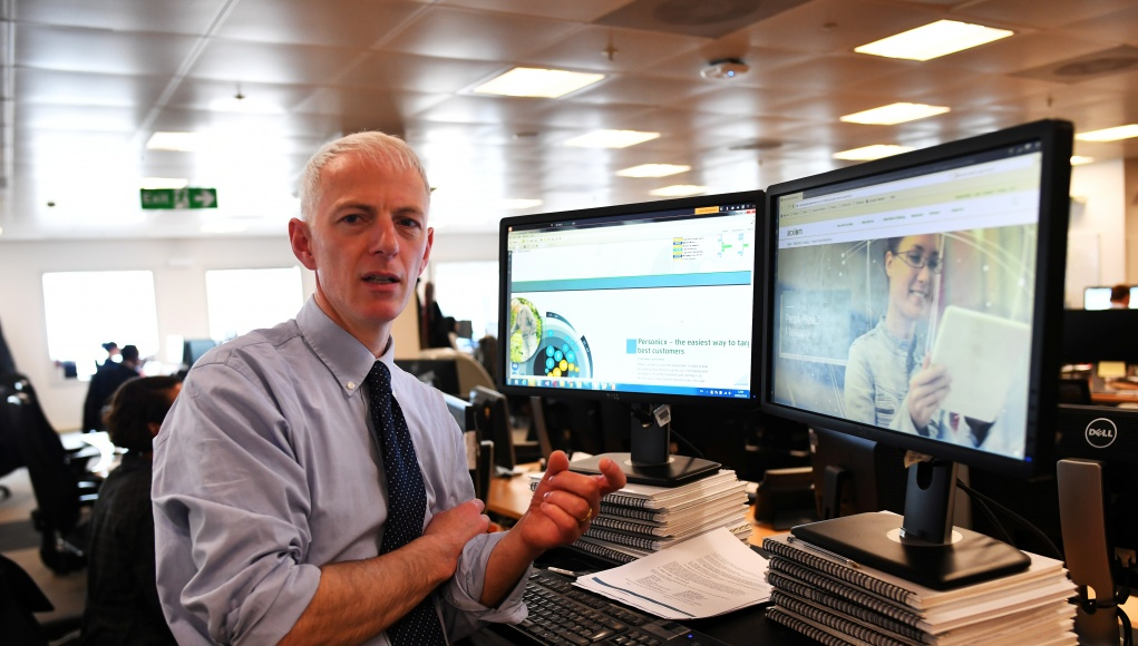 Reuters journalist Tom Bergin poses next to his screens showing marketing technology company Acxiom's website, in London