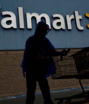 Employee arranges shopping carts in front of the logo of Walmart outside a store in Monterrey