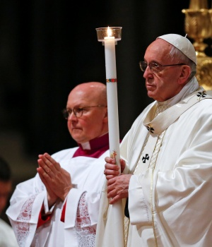 Pope Francis holds a candle as he leads the Easter vigil mass in Saint Peter's Basilica at the Vatican