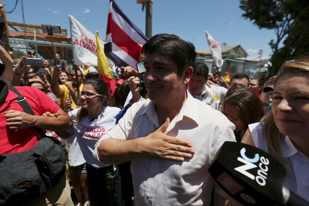 Carlos Alvarado Quesada, presidential candidate of the ruling Citizens' Action Party, gestures to supporters after casting his ballot during the presidential election in San Jose