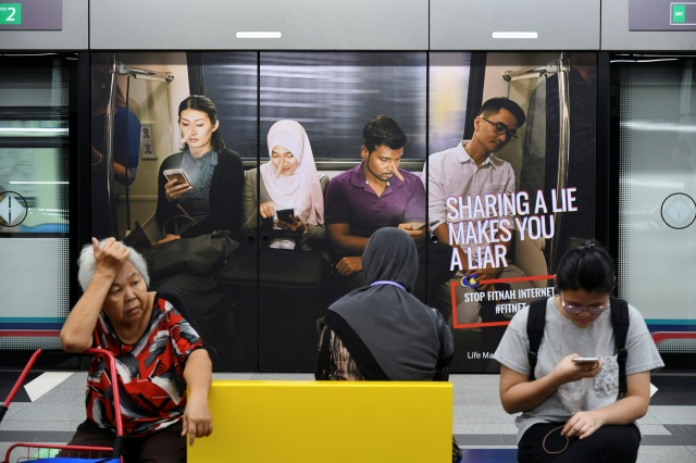 Commuters sit in front of an advertisement discouraging the dissemination of fake news, at a train station in Kuala Lumpur