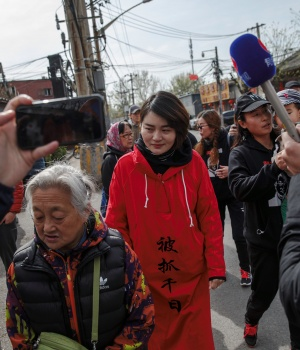 Li Wenzu, wife of detained Chinese rights lawyer Wang Quanzhang, is followed by friends and media near a Supreme People's Court complaints office in Beijing