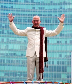 Jeff Bezos, founder and CEO of Amazon, poses as he stands atop a supply truck during a photo opportunity at the premises of a shopping mall in Bangalore