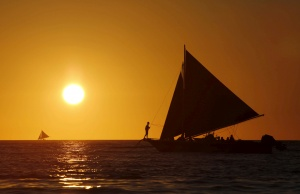 Tourists catch a glimpse of the sunset while sailing along the island of Boracay, central Philippines