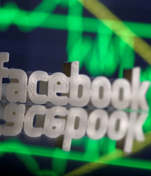 A 3D-printed Facebook logo is seen in front of displayed stock graph