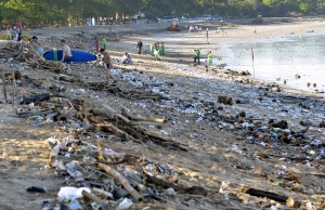 Tourists walk amongst trash washed up on Kuta beach by seasonal winds, as workers attempt a clean-up in the background, on the Indonesian island of Bali