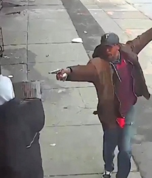 Saheed Vassell points a metal pipe at a pedestrian in Brooklyn in a still image from surveillance video released by the New York Police Department