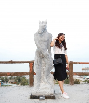A woman poses for a photo near godlike sculptures with animal heads and human genitalia at Hon Dau resort in Hai Phong city, east of Hanoi