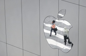 A woman is reflected in a Apple store logo in San Francisco