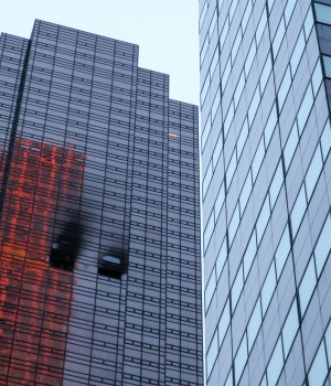 Damaged windows are seen after a fire in a residential unit at Trump Tower in New York