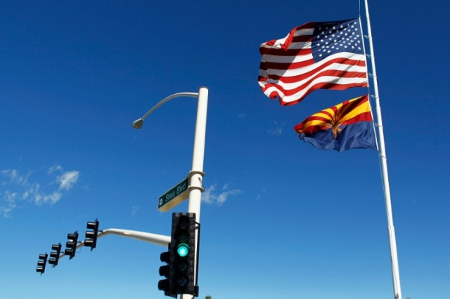 The U.S. and Arizona flags flutter in the wind in Fountain Hills