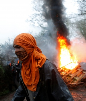 A protestor walks past burning debris as French gendarmes continue an evacuation operation in the zoned ZAD (Deferred Development Zone) in Notre-Dame-des-Landes
