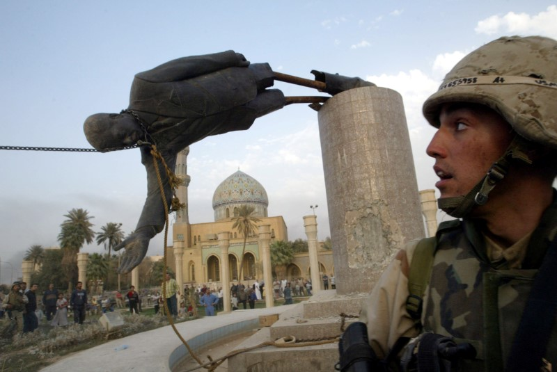 U.S. soldier watches as statue of Iraq's President Saddam Hussein falls in central Baghdad