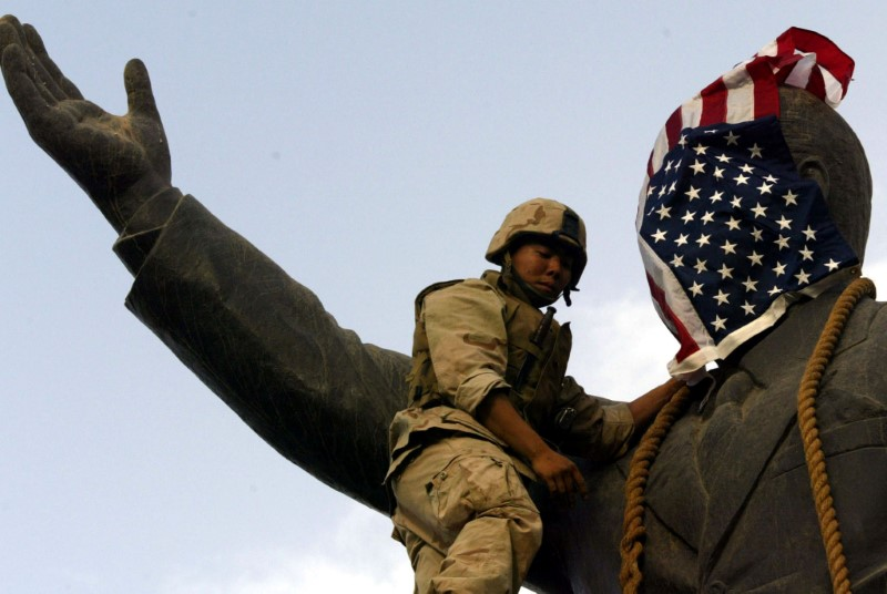 U.S. Marine covers face of Iraqi President Saddam Hussein statue with U.S. flag in Baghdad