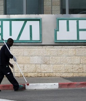 A man cleans near the logo of Teva Pharmaceutical Industries at their plant in Jerusalem