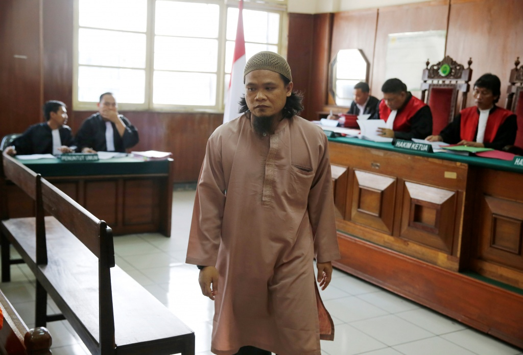 Kiki Muhamad Iqbal, convicted of masterminding suicide bombings at Jakarta's bus terminal in 2017, walks through the courtroom during his trial in Jakarta