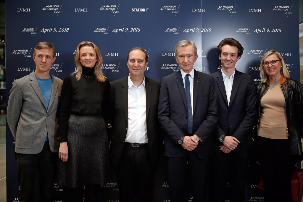 "Ian Rogers, Delphine Arnault, Xavier Niel, Bernard Arnault, Frederic Arnault and Chantal Gaemperle pose for a photograph at ""Station F"", a mega-campus for startups located inside a former freight railway depot in Paris"
